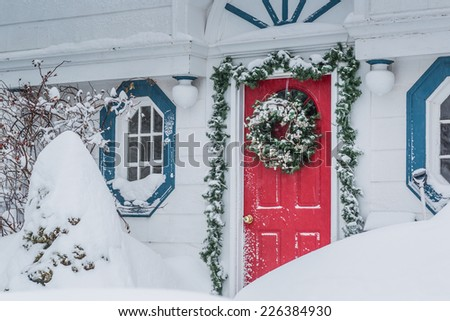 A red door decorated for Christmas in a snow storm. - stock photo