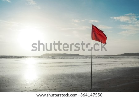 A red flag as a danger warning sign on the beach. Shining sun in the background. - stock photo