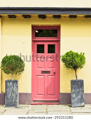 A red front door in a yellow cottage in England - stock photo