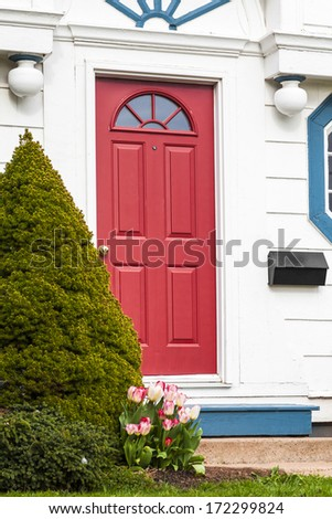 A red front door of an older traditional style American type home. - stock photo