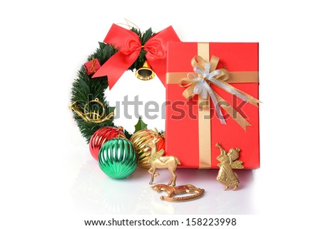 A red gift box with Christmas accessory on white background.