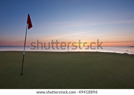 A red golf flag on a green with the sun rising over the sea in the background. Photo taken on a spring morning on the new Castle Course in St Andrews. - stock photo