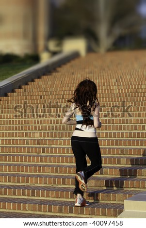 A red haired woman running up brick stairs in workout clothes - stock photo