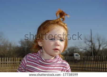 A red headed blue eyed little girl with her hair in a pony tail.