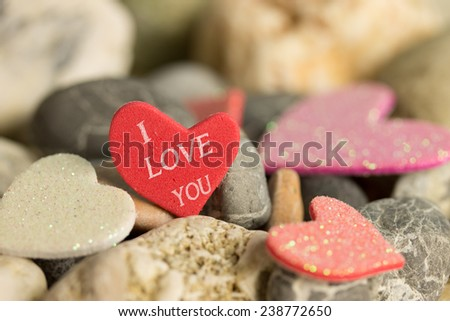 a Red heart between multi colored natural stones - stock photo