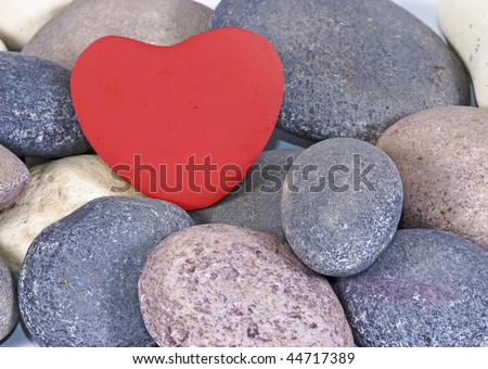 a Red heart made of stone on natural colored stones - stock photo