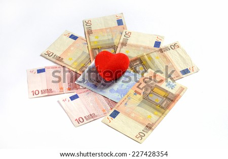 a red heart on a pile euro banknotes depicting the idea of love for the money - stock photo