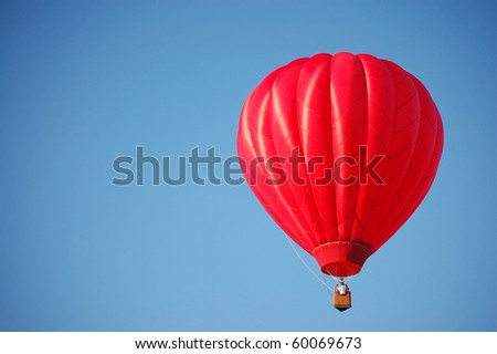 A red hot-air balloon in the sky on a beautiful summer morning.