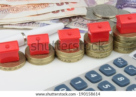 A red houses sitting on a coins, with a pen and calculator to symbolize house finance in the U.k. - stock photo