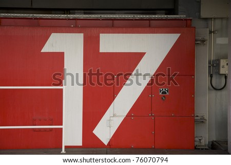 a red japanese tsunami watertight door in osaka bay area with the number 17 painted on it - stock photo
