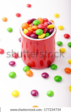 A red jar with colorful hard candies - stock photo