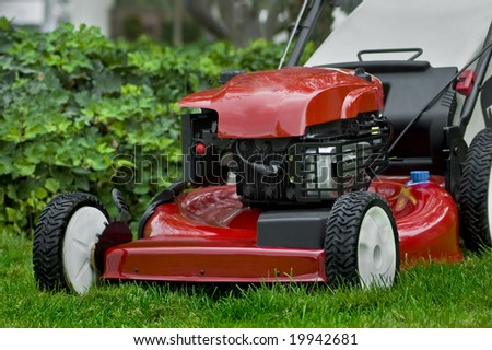 A red lawnmower sits on the grass by some ivy. - stock photo