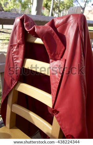 A red leather coat hanging on a chair.