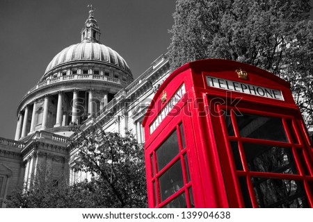 A red London phone box with a black and white St Paul's Cathedral in the background - stock photo