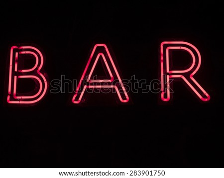 """A red neon sign that says """"BAR"""". - stock photo"""