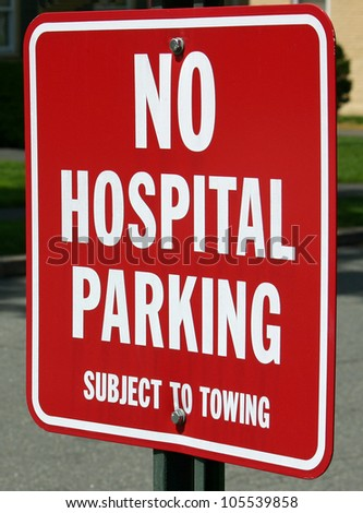 A red No Parking sign on a street near a hospital - stock photo