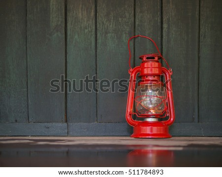 a red old lantern on the dark wet wooden floor with reflection on the floor