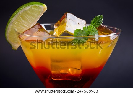 a red orange cocktail with lime slice