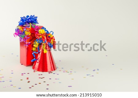 A red party hat and a gift with ribbons,bows and confetti - stock photo