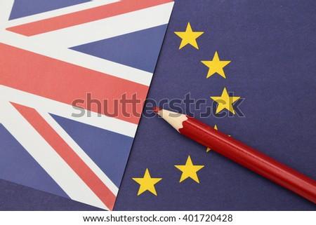 A red pencil on a European an British flag - stock photo