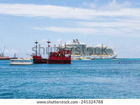 A red pirate ship in harbor of Philipsburg, St Marting with cruise ship in background