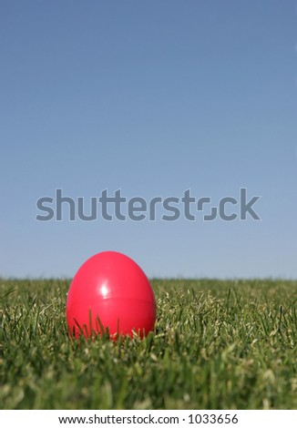 A red plastic Easter egg on the grass with a blue sky - shallow DOF.