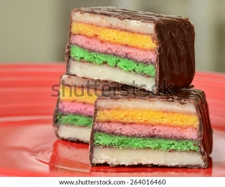 A red plate with three petit fours, colorful cake layers with marzipan