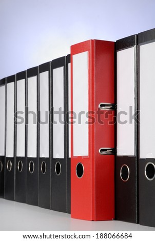 A red ring binder between a row of black files. - stock photo