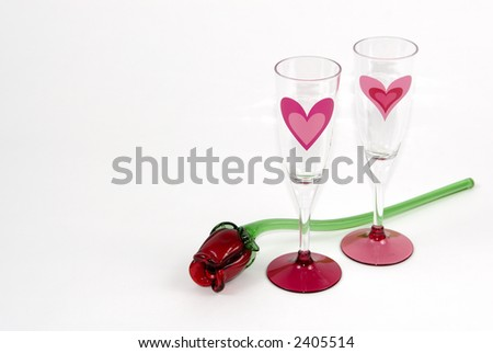 A red rose and two champaign glasses isolated on white with room for text. - stock photo