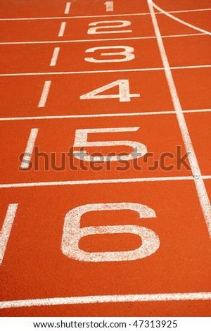 A red running track with lane numbers painted upwards - stock photo
