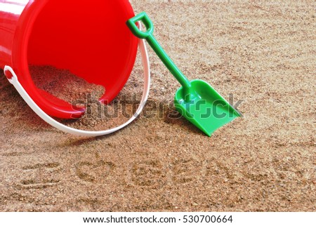 A red sand pail and shovel at th beach.