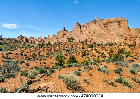 A red sandstone monolith stands atop a hill in Arches National Park, Utah.