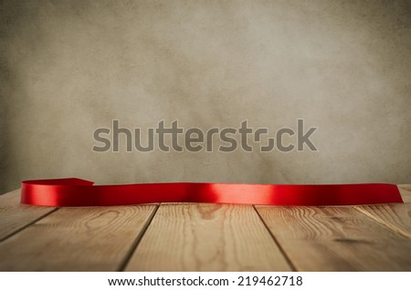 A red satin ribbon, curved and facing front to provide copy space for message, placed on a wood plank table against parchment background.  Vintage style. - stock photo