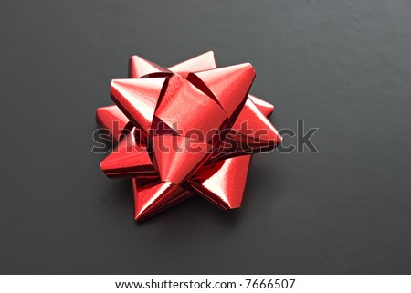 A red, shiny bow isolated on black background.