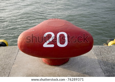 a red ship bollard by the dock with the number 20 painted on it - stock photo