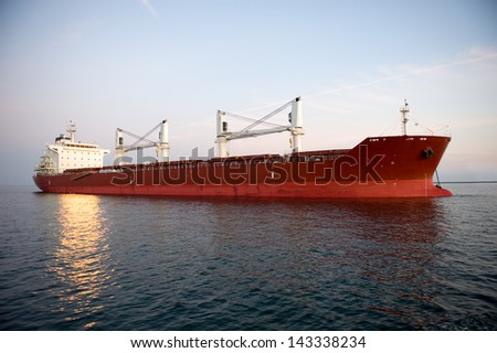 A red shipping transportation freighter anchored just inside a port of call. - stock photo