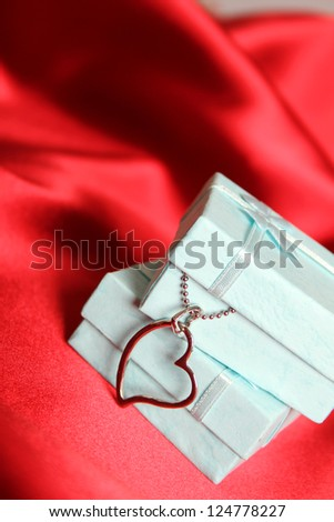 A red silk greeting card and gift boxes with silver decoration.