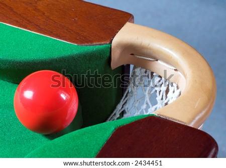 A red snooker ball balanced at a corner pocket - stock photo
