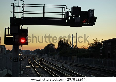 A red stop signal next to railway lines heading West at sunset.  Basingstoke railway station, Hampshire, UK. - stock photo