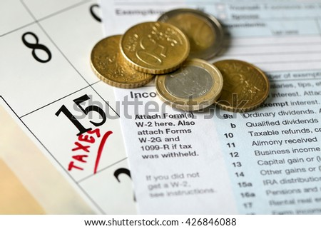 A red tax mark in the calendar, euro coins and tax form, close up - stock photo