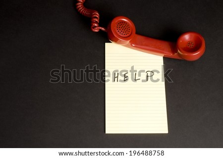 A red telephone receiver lying on a paper with 'HELP' written on it. - stock photo