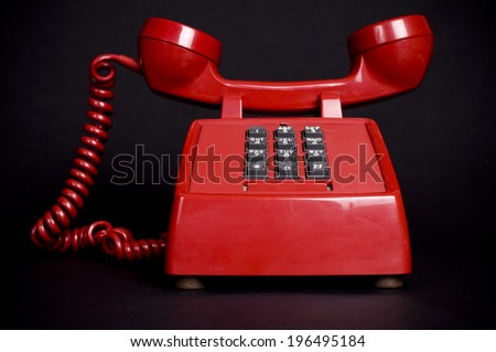 A red telephone with the receiver upside down. - stock photo