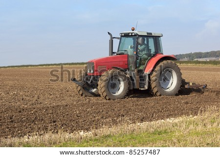 a red tractor cultivating fields on a hillside in autumn
