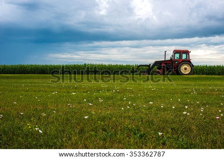 A red tractor on a bright green landscape.