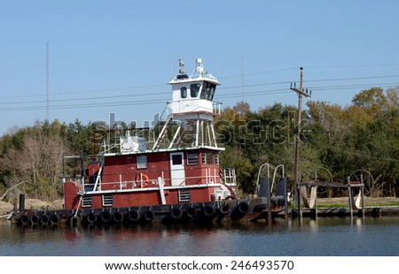 A red tugboat docked on Bayou Lafourche in Southern Louisiana. - stock photo