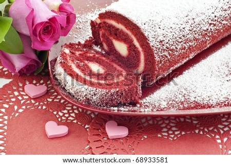 A red velvet cake roll sliced on a plate with pink roses and hearts, great for Valentine's Day