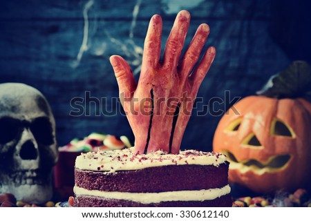 a red velvet cake topped with a bloody hand in a scary scene for halloween with a carved pumpkin, a skull and cobwebs - stock photo