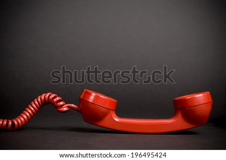 A red vintage telephone receiver with a spiral cord. - stock photo