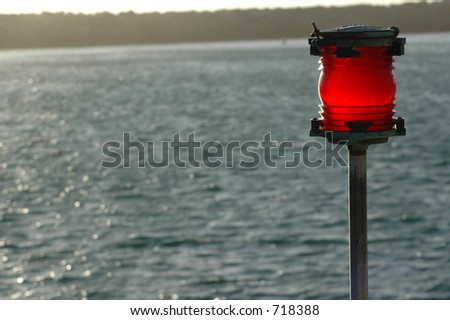 A red warning beacon in the late afternoon sun near the ocean sea-wall.