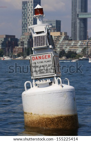 """A Red Warning Buoy Navigational Aid That Reads, """"Danger Low Flying Planes Vessels Keep Out Violators Subject To Prosecution."""" - stock photo"""
